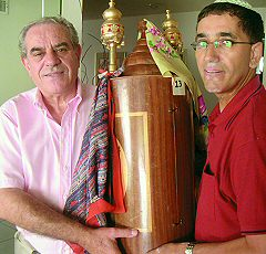 Avi Dahan, left, and Nisim Dadon, two founders of the Scottsdale Sepharadic Synagogue, hold a Torah that was originally dedicated by Dahan's grandmother at a Jerusalem synagogue.