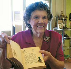 "Ruth Cohen, director of the Brandeis Book Shoppe and board member of the Phoenix chapter, displays one of the rare books donated to the bookstore. This book, ""Wee Drappies"" by Sir Harry Lauder, was published in 1932 and features an empty scotch bottle which fits into the book's pages."